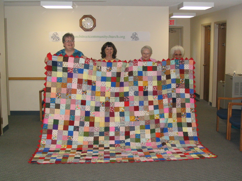 Crafty Ladies Showing Off The Quilt They Made.