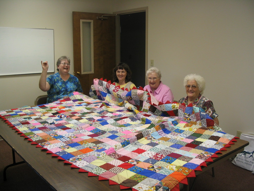 Crafty Ladies Sewing The Quilt.